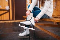 La persona femenina que se sienta en banco y lleva patines Foto de archivo