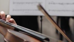 La persona gioca su fiddle davanti ad un foglio di carta con le note musicali su un fondo vago all'interno stock footage