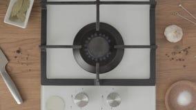 La persona gira la estufa de gas y pone la cacerola del metal con agua en ella metrajes