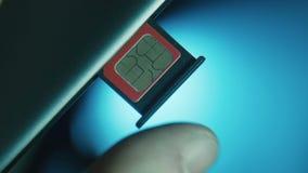 La persona instala la ranura con la tarjeta de SIM almacen de metraje de vídeo