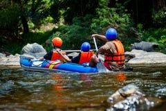 La persona joven está transportando en balsa en el río con el ayudante del viaje de la guía Imágenes de archivo libres de regalías