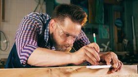 La persona lavora con legno, facendo uso della matita e di un righello Funzionamento anziano del carpentiere video d archivio