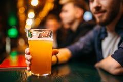 La persona masculina sostiene el vidrio con la cerveza en el contador de la barra Foto de archivo libre de regalías