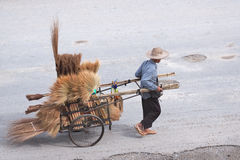 La persona masculina transporta las escobas Foto de archivo