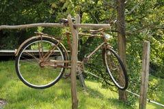 La persona mayor, bicicleta oxidada, cuelga en un haz de madera Fotografía de archivo