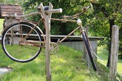 La persona mayor, bicicleta oxidada, cuelga en un haz de madera Fotografía de archivo libre de regalías