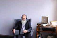 La persona mayor masculina goza el escuchar la música rock en los auriculares Imagenes de archivo