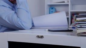 La persona ocupada del negocio hojea las páginas del registro que consideran que buscan la información almacen de metraje de vídeo