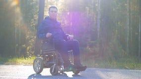 La persona parapléjica se está sentando en una silla de ruedas exterior y está mirando en la cámara almacen de video