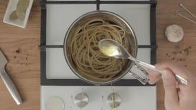 La persona pone la cuchara llena del aceite en cacerola del metal con espaguetis hervidos almacen de video