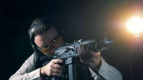 La persona practicante se coloca con un rifle de asalto, cierre para arriba Rifle de asalto del Kalashnikov almacen de video