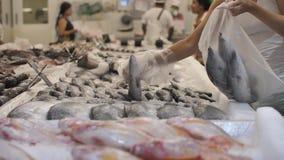 La persona prende il pesce crudo fresco nel dipartimento del pesce del deposito stock footage