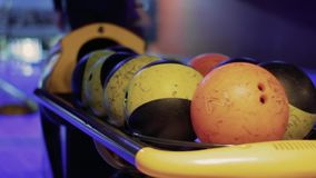 La persona prende le palle da bowling con il vicolo di bowling nel fondo archivi video