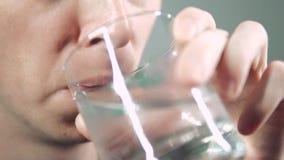 La persona prende la medicina beve la pillola con acqua in un vetro video d archivio