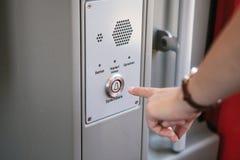 La persona presiona el botón para llamar y para hablar con el servicio de asistencia del tren o del subterráneo imagen de archivo