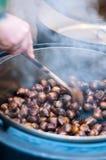 La persona produce la castagna arrostita Fotografie Stock