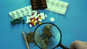 La persona que mira los brotes médicos de la marijuana con la lupa Las píldoras están en el fondo almacen de metraje de vídeo