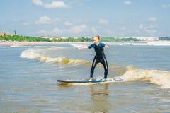 La persona que practica surf alegre del principiante de la mujer joven con resaca azul se divierte en sma foto de archivo