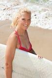 La persona que practica surf atractiva joven lleva a cabo a una tarjeta en la playa Fotografía de archivo