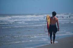 La persona que practica surf camina abajo de la playa arenosa que busca un buen lugar para practicar surf en Jacksonville, la Flo Fotos de archivo