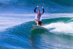 La persona que practica surf celebra la salida del paseo de la onda Foto de archivo libre de regalías