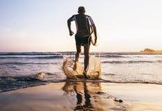 La persona que practica surf con la tabla hawaiana se rueda a las olas oceánicas Fotos de archivo libres de regalías
