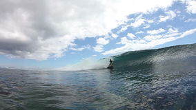 La persona que practica surf consigue Barreled en onda azul almacen de video