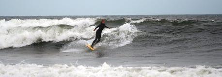 La persona que practica surf de la muchacha monta las ondas Imagenes de archivo