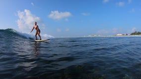 La persona que practica surf de la muchacha monta la ola oceánica almacen de video