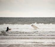 La persona que practica surf de sexo femenino limpia hacia fuera Imagen de archivo libre de regalías