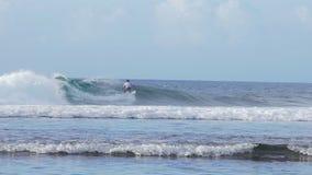 La persona que practica surf del Balinese monta una ola oceánica tropical en Bali Indonesia en la cámara lenta almacen de video