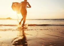 La persona que practica surf del hombre corre en el océano con la tabla hawaiana en luz de la puesta del sol Fotografía de archivo libre de regalías
