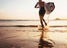 La persona que practica surf del hombre corre en el océano con la tabla hawaiana en luz de la puesta del sol Foto de archivo