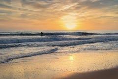 La persona que practica surf en el mar en el tablero, un fondo de la puesta del sol monta Fotos de archivo