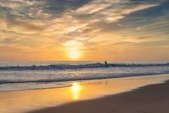 La persona que practica surf en el mar, en un fondo de la puesta del sol monta Imagenes de archivo