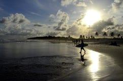 La persona que practica surf en una playa famosa en el Brasil en la puesta del sol, Praia hace Francês, ³ de MaceiÃ, el Brasil Fotografía de archivo