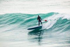 La persona que practica surf encendido se levanta el tablero de paleta en onda azul Invierno que practica surf en el océano foto de archivo libre de regalías