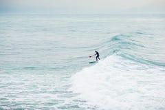La persona que practica surf encendido se levanta el tablero de paleta en onda azul Invierno que practica surf en el océano Foto de archivo