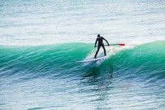 La persona que practica surf encendido se levanta el tablero de paleta en onda azul Paleta que practica surf en el océano Imagen de archivo