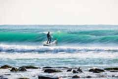 La persona que practica surf encendido se levanta el tablero de paleta en onda azul SORBO que practica surf en el océano fotos de archivo libres de regalías