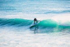 La persona que practica surf encendido se levanta el tablero de paleta en onda Invierno que practica surf en el océano Fotografía de archivo