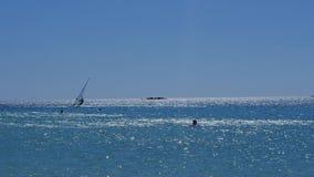 La persona que practica surf está flotando en las ondas Fotos de archivo libres de regalías
