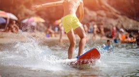 La persona que practica surf joven del novato en pantalones cortos amarillos aprende coger la onda en tablero rojo de la orilla S fotografía de archivo libre de regalías