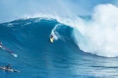 La persona que practica surf monta la onda gigante en los mandíbulas Foto de archivo