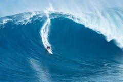 La persona que practica surf monta la onda gigante en los mandíbulas Imágenes de archivo libres de regalías
