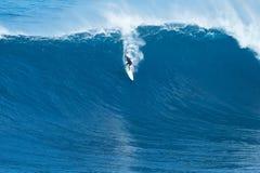 La persona que practica surf monta la onda gigante en los mandíbulas Imagen de archivo libre de regalías