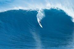 La persona que practica surf monta la onda gigante en los mandíbulas Imagen de archivo