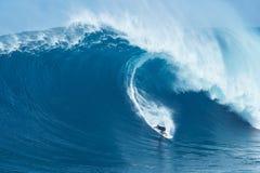 La persona que practica surf monta la onda gigante en los mandíbulas Foto de archivo libre de regalías