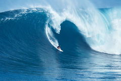 La persona que practica surf monta la onda gigante en los mandíbulas Fotografía de archivo
