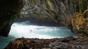 La persona que practica surf navega entre las rocas peligrosas de la bahía almacen de video